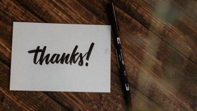 Palavra obrigada escrita em inglês em um papel branco