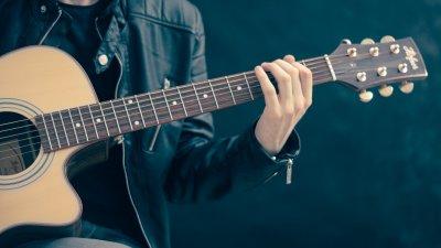 Foto de pessoa trocando violão
