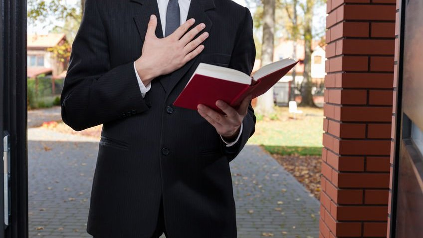 Jovem vestindo terno e gravata, com a mão direita no peito, e a mão esquerda segurando uma bíblia aberta.