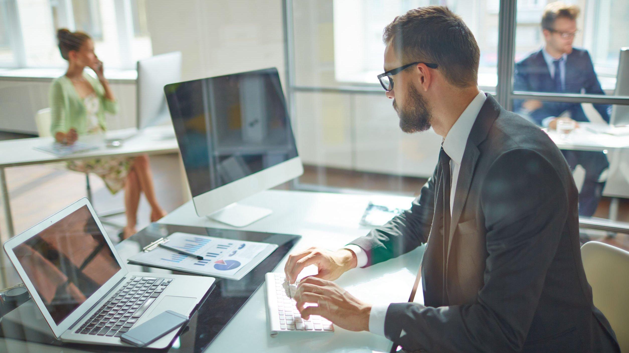 Homem em escritório, digitando em teclado de computador,