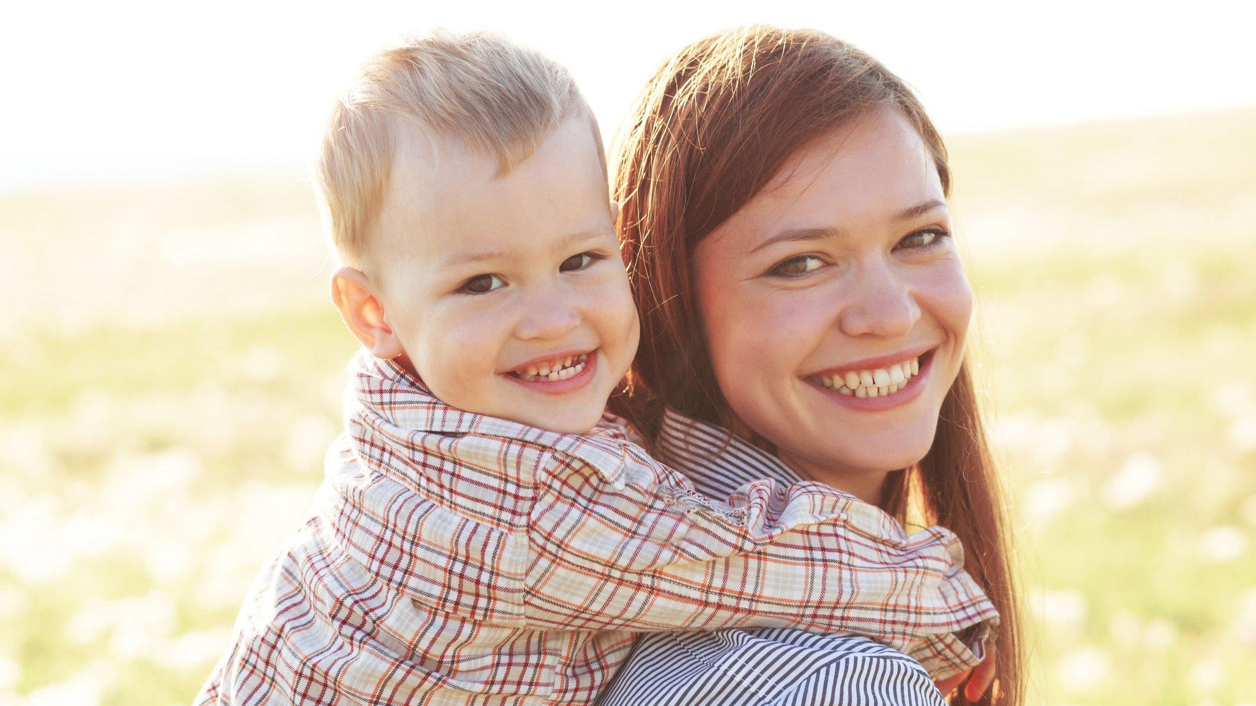 Mulher carregando menino em suas costas, que a abraça no pescoço. Ambos sorriem para a câmera.