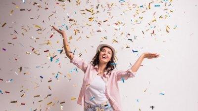 Mulher sorrindo com confetes caindo