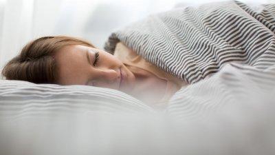 Pessoa dormindo com os pés para fora da cama e do edredom. Ao lado dos pés, um cachorrinho branco está deitado e acordado.