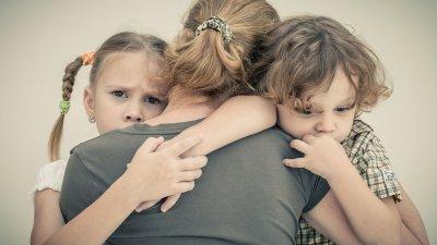Foto de mãe abraçando filhos