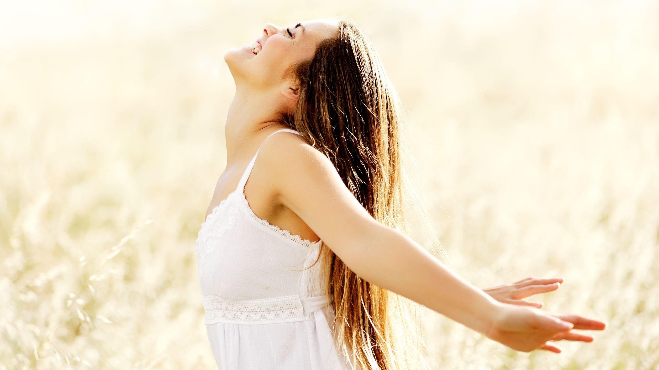 Mulher sorrindo de braços abertos em um campo.