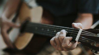 Homem tocando violão com pessoas em sua volta