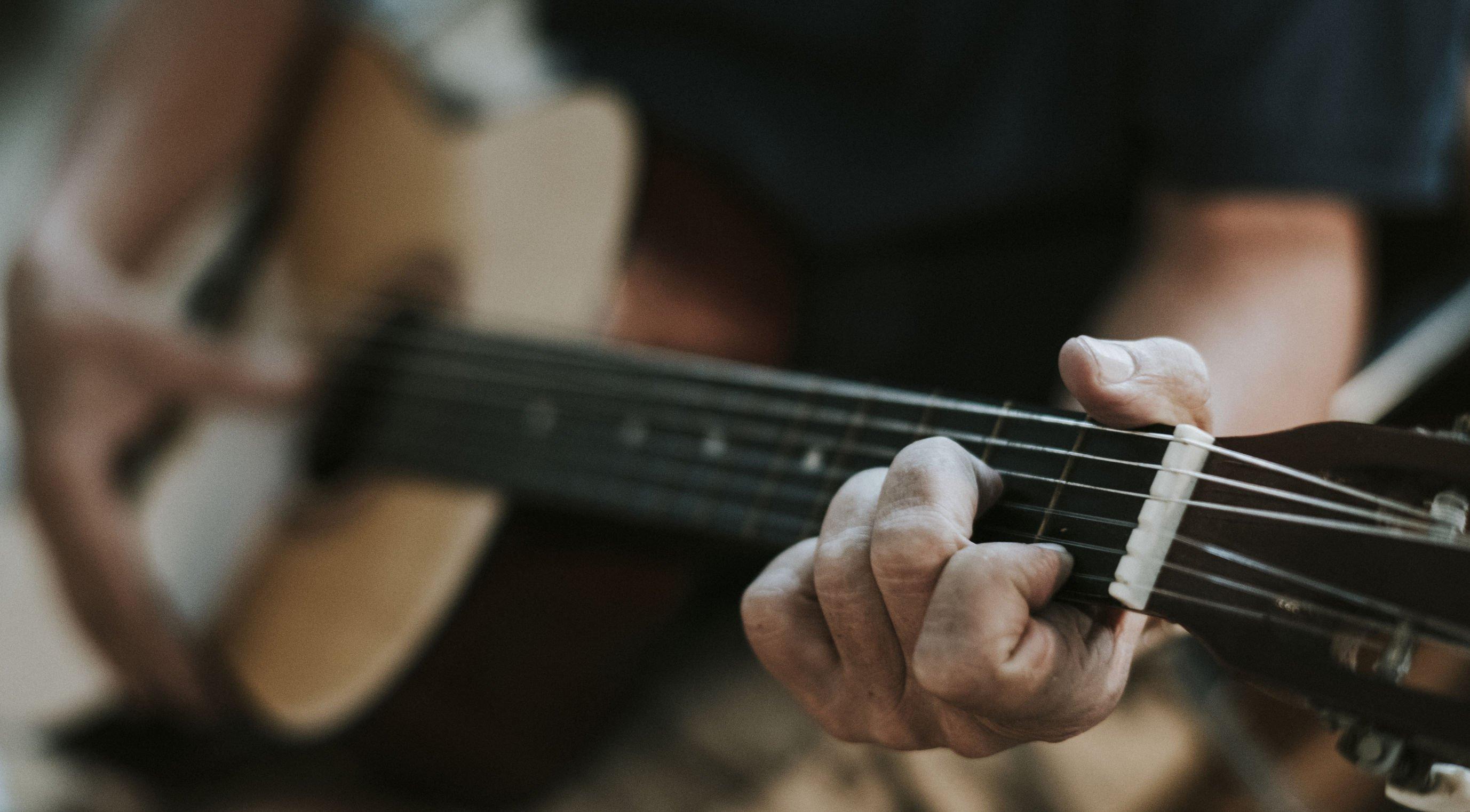 Homem branco tocando violão.