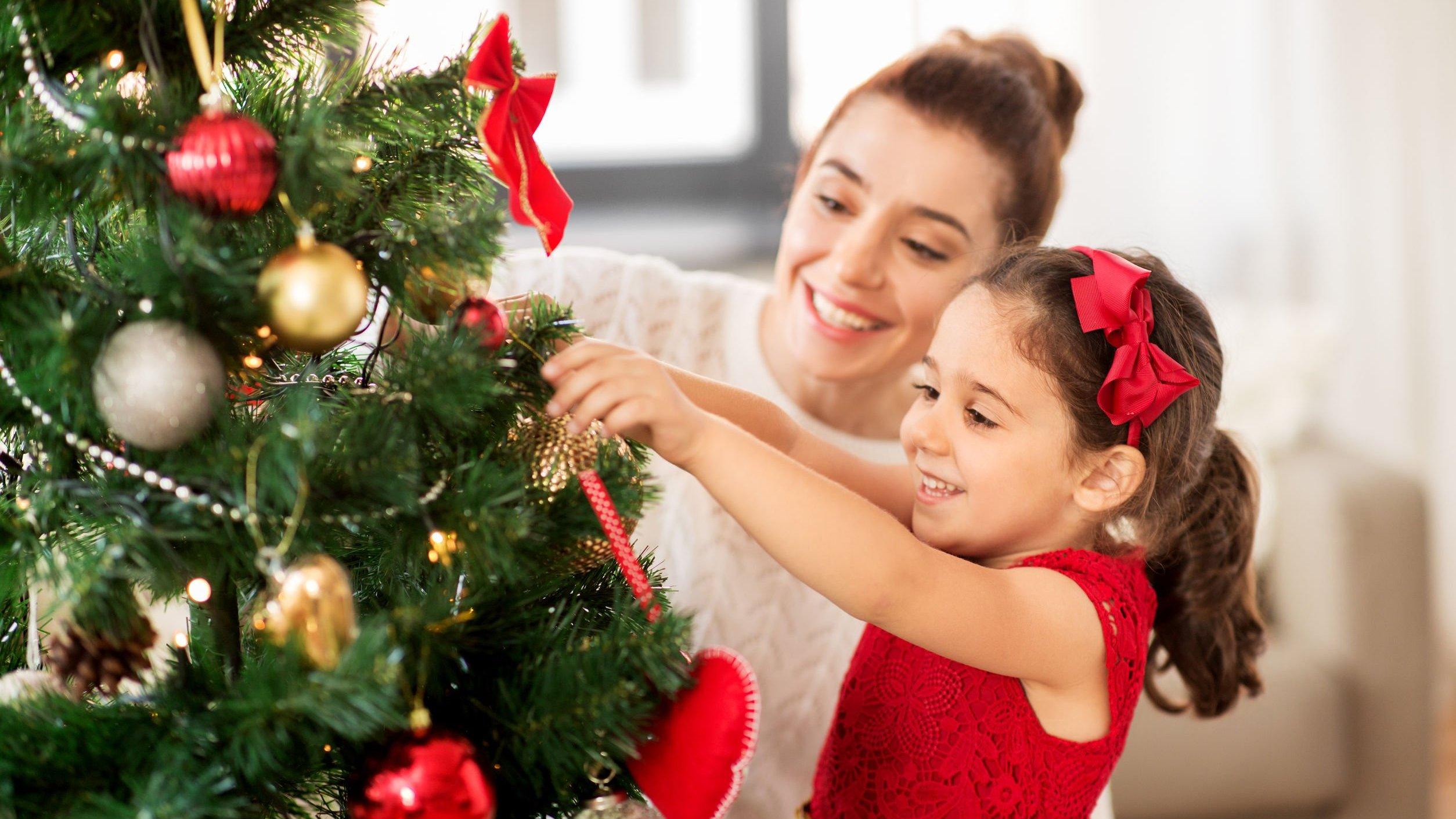 Mãe e filha felizes decorando arvore de natal