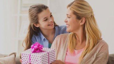 Menina sorrindo ao olhar para mulher segurando presente