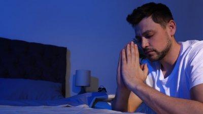 Homem ajoelhado à beira da cama em oração