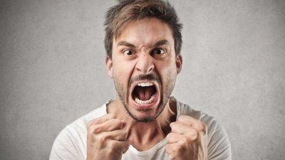 Homem com os punhos cerrados, boca aberta e franzindo a testa, como se estivesse gritando.