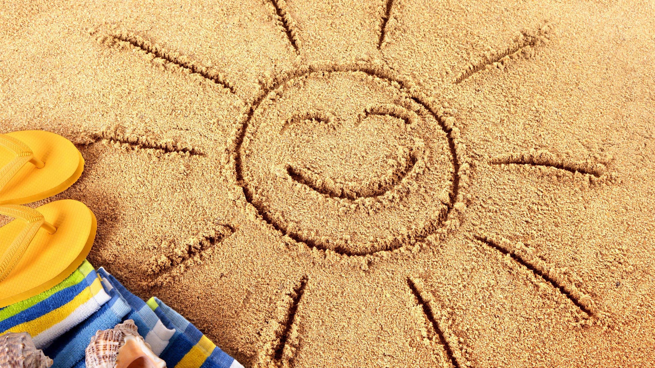 Foto de sol desenhado em areia de praia