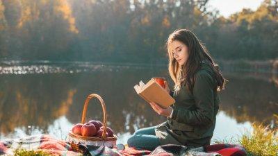 Garota lendo livro em meio a natureza