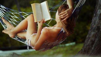 Mulher deitada na rede lendo um livro