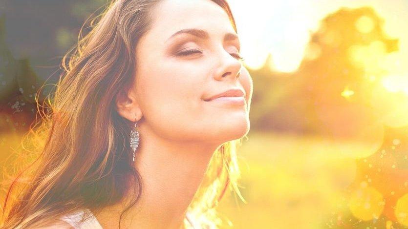Mulher sorrindo com os olhos fechados