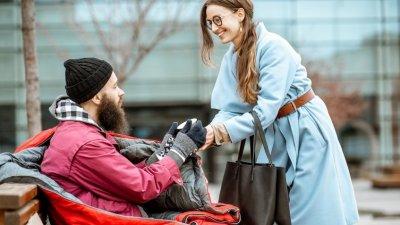 Mulher entregando um copo de café para um morador de rua