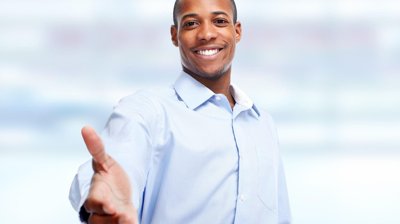 Foto de pessoa simpática, sorrindo e oferecendo a mão