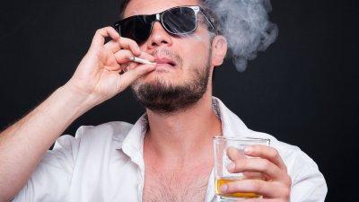 Foto de pessoa malandra fumando charuto e segurando bebida
