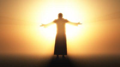 Silhueta de um religioso com os braços abertos.