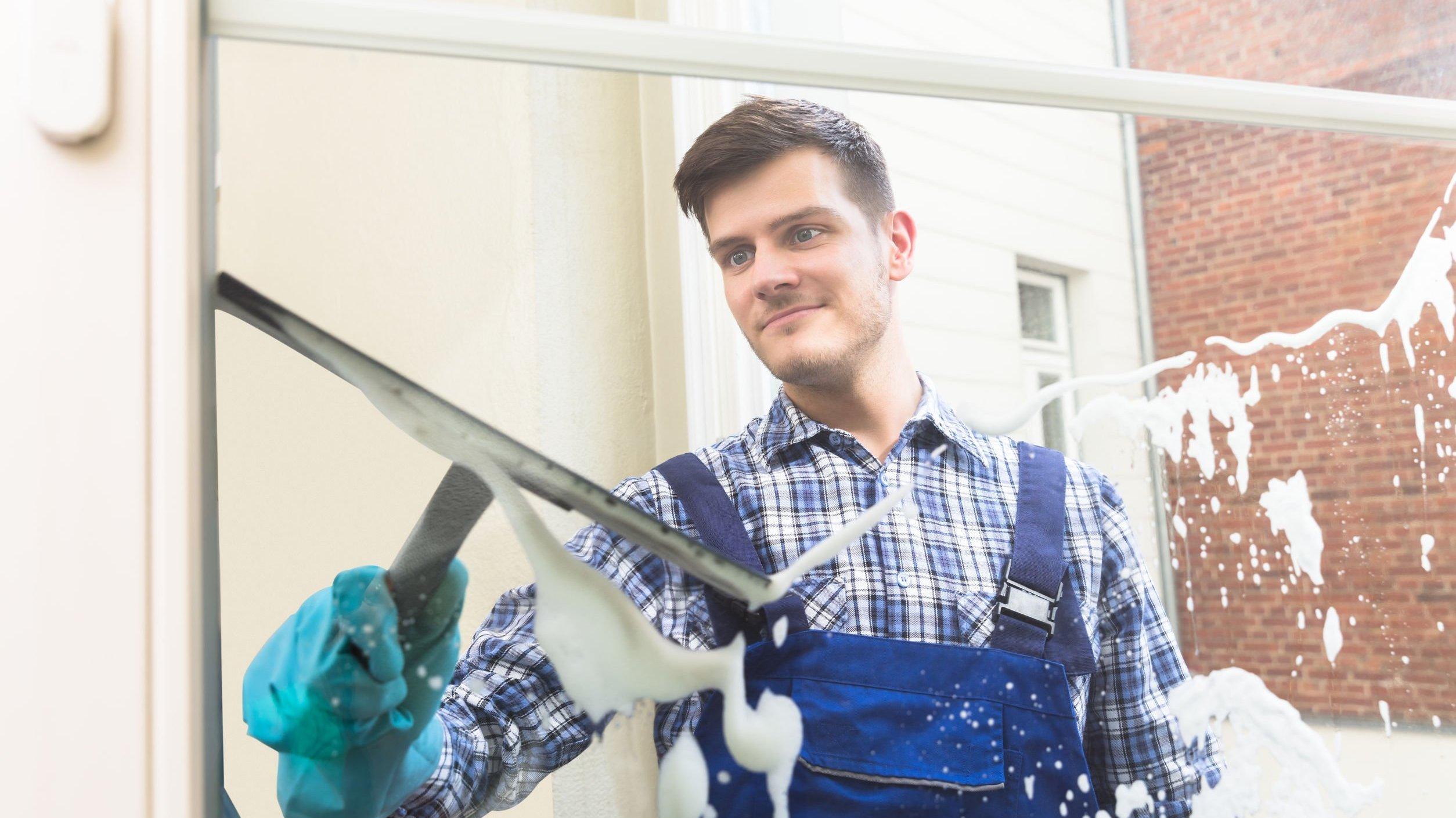 Foto de zelador limpando vidro