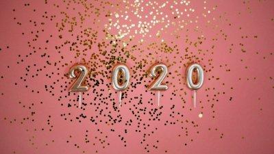 Fundo rosa com brilhos dourados espalhados, e quatro velas, cada uma com um número, escrevendo 2020.