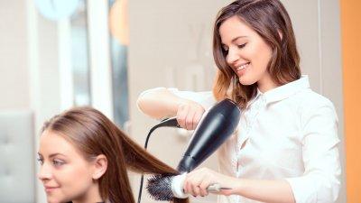 Cabeleireira fazendo escova no cabelo da cliente