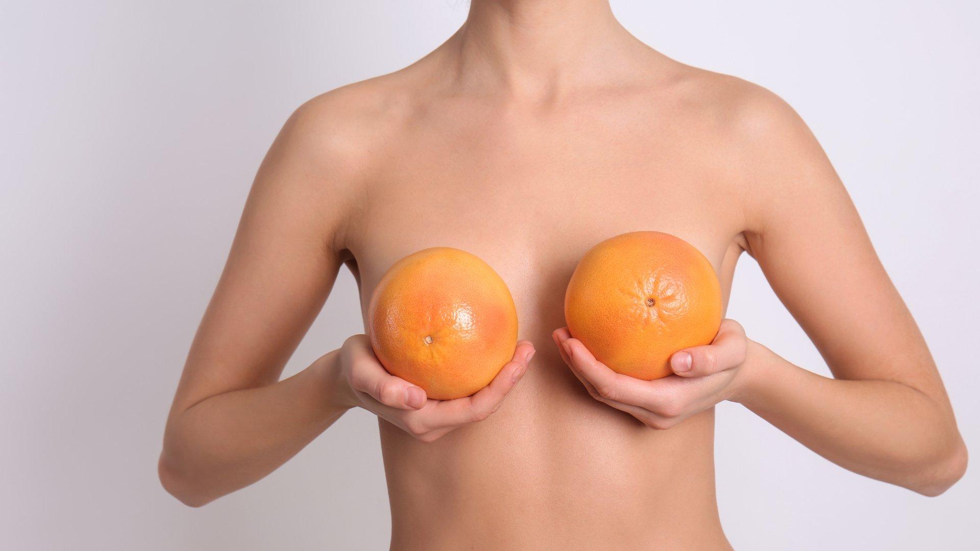 Mulher segurando duas laranjas em frente aos seios