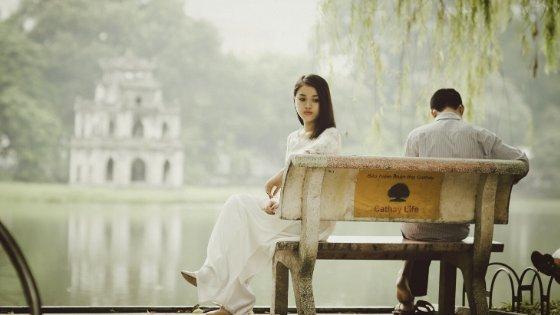 Mulher distante de marido sentado no mesmo banco