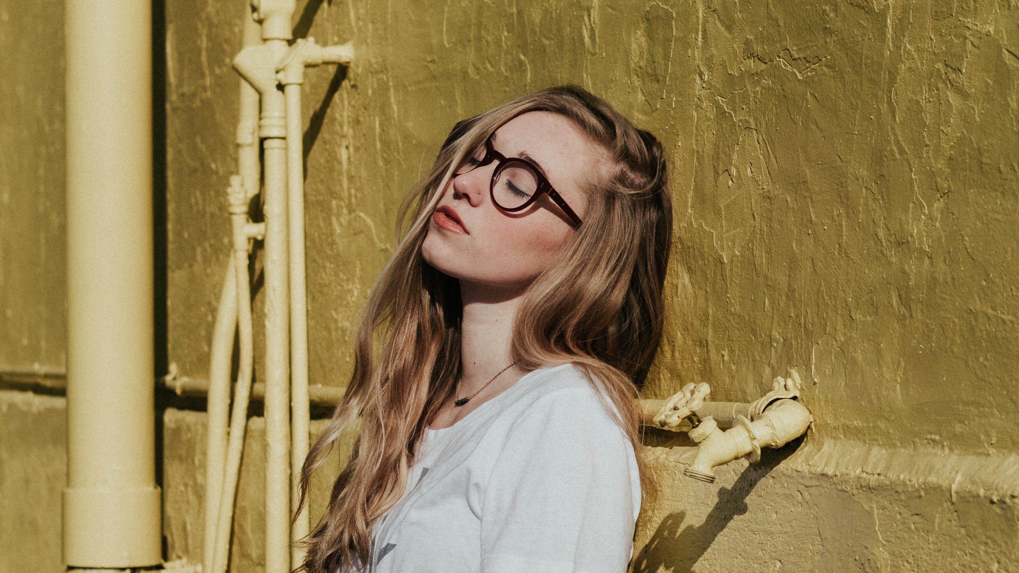 Mulher de óculos encostada em uma parede com os olhos fechados.