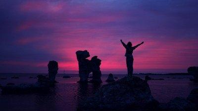 Pessoa de braços abertos sobre pedra