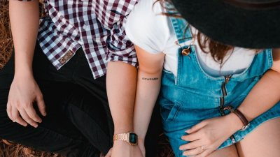 Casal sentados de mãos dadas.