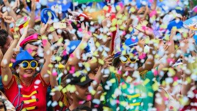 Pessoas comemorando o Carnaval em bloco, com fantasias e confete.