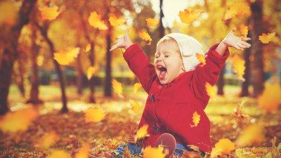 Menina pequena sentada em folhas secas caídas no chão, com os braços para o alto, e a boca aberta em uma risada.
