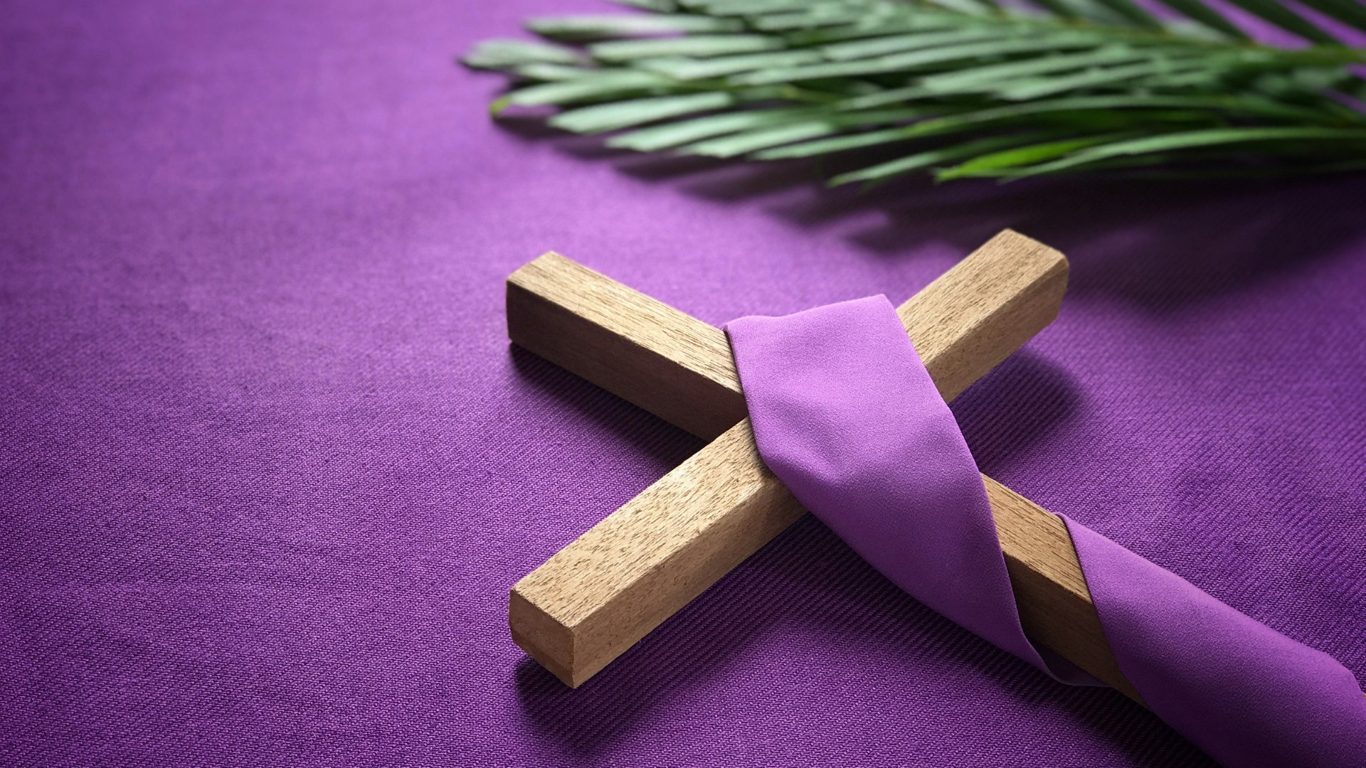 Cruz de madeira enrolada em tecido roxo