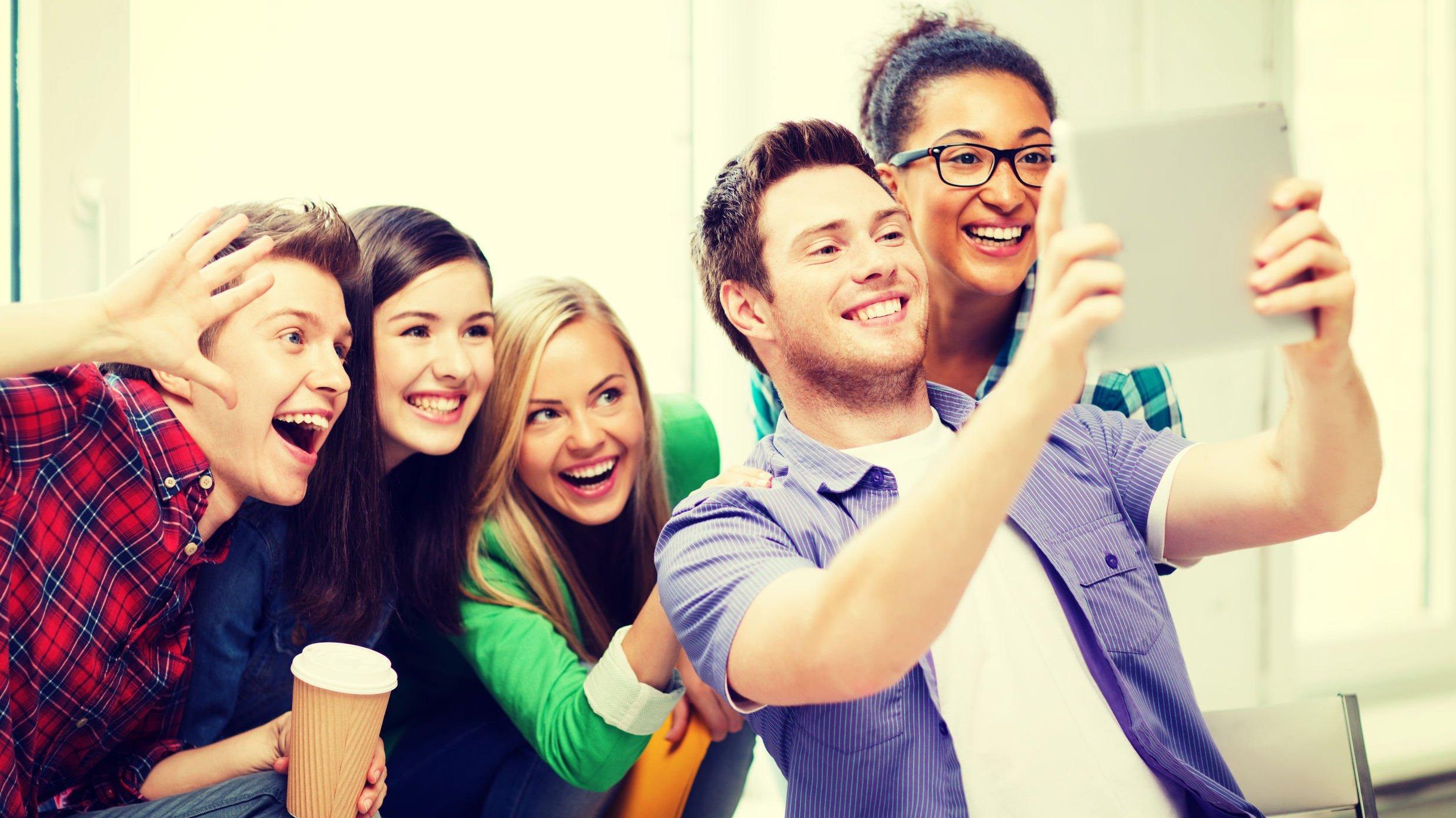 Grupo de amigos posando para uma selfie que o homem da frente irá tirar com um tablet.