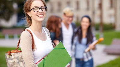 Aluna da faculdade segurando pasta e caderno sorrindo