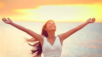 Mulher de braços abertos com o mar e o pôr do sol atrás