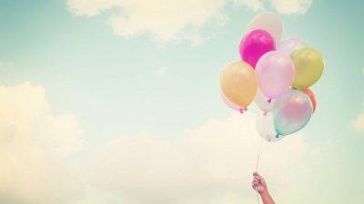 Mão segurando balões coloridos com céu ao fundo