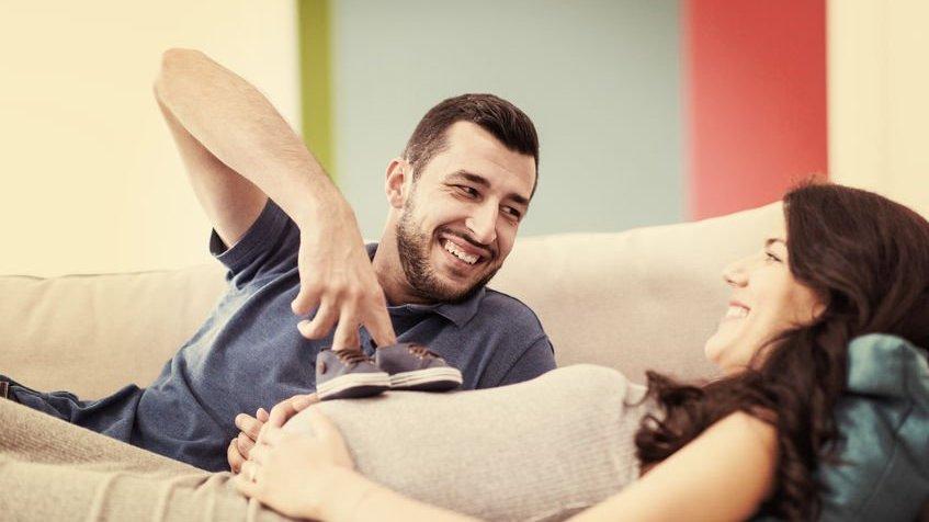 Homem sorridente segurando dois sapatinhos de bebê na barriga de mulher gestante.