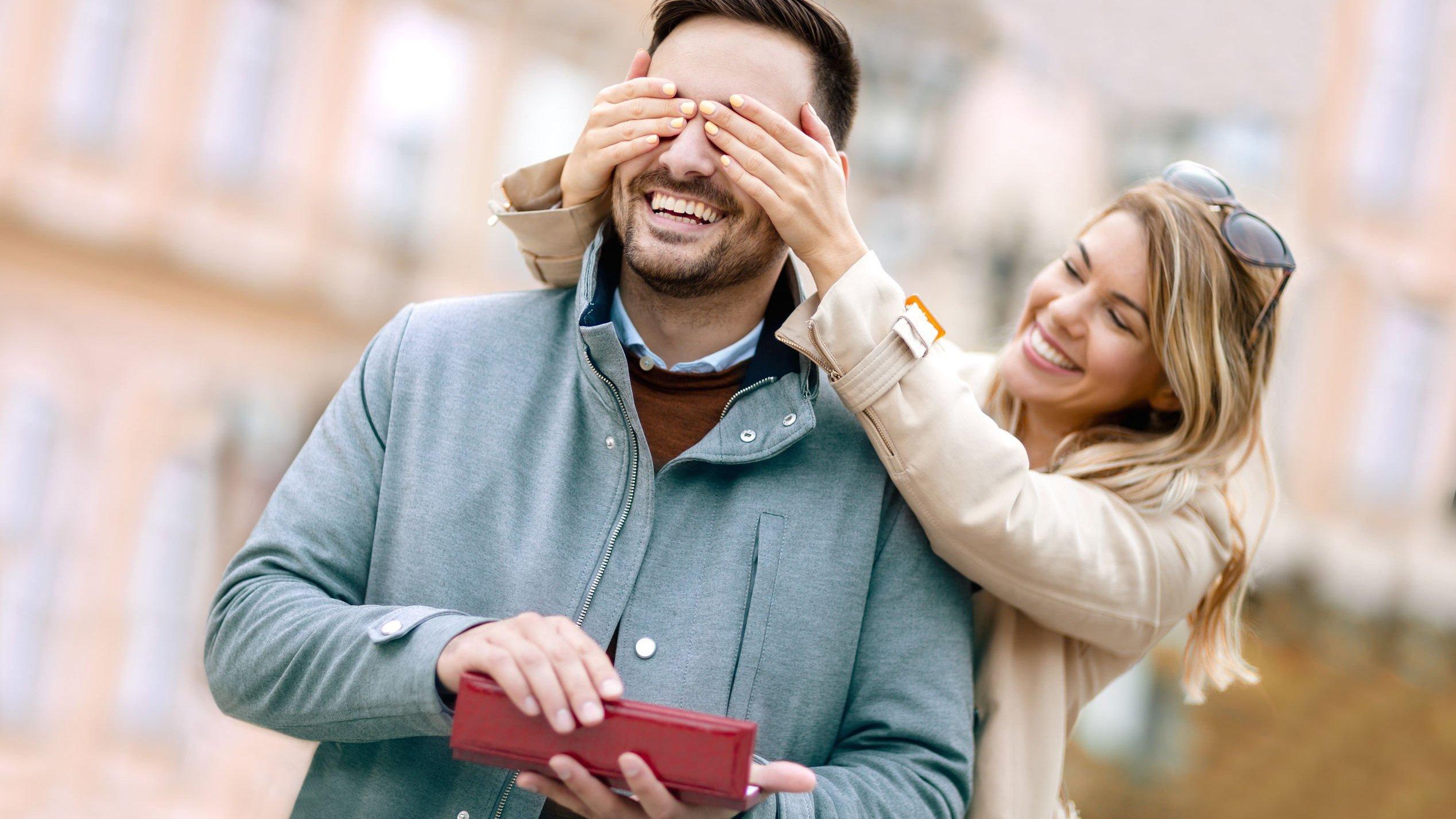 Mulher cobrindo os olhos do homem enquanto ele segura caixa de presente