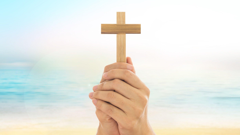 Mãos segurando uma cruz em frente ao mar.