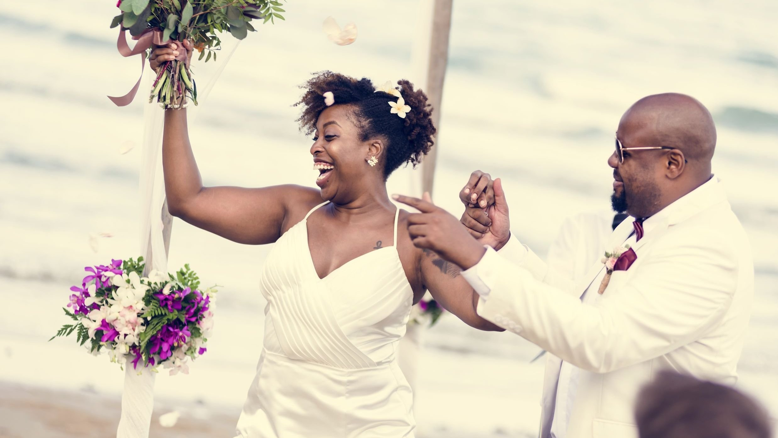 Homem e mulher se casando na praia, o noivo aponta para algo e a noiva sorri segurando seu buquê para o alto.