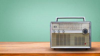 Rádio antigo com alça em cima de móvel de madeira.