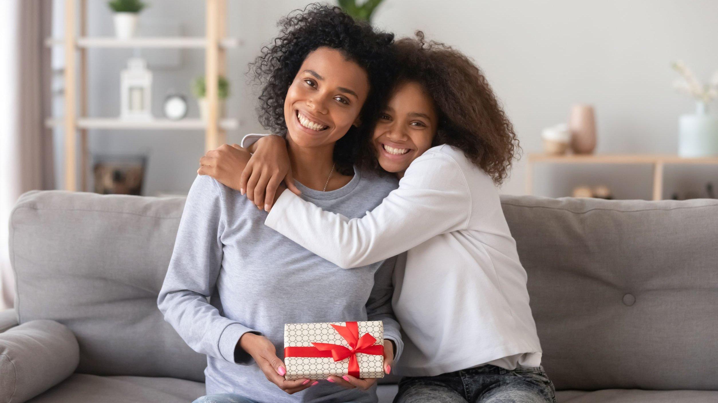 Filha abraça mãe, que segura um presente.