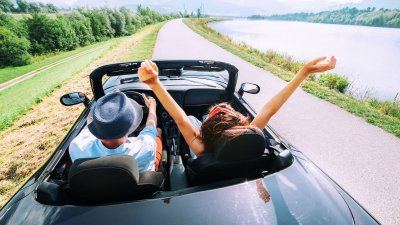 Homem e mulher em carro conversível. O homem dirige e a mulher está com os braços para o alto.