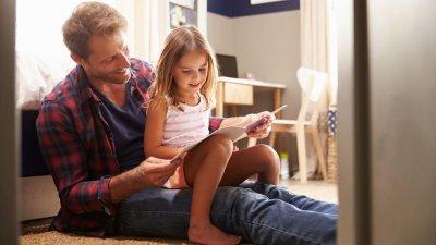 Pai com filha no colo lendo livro