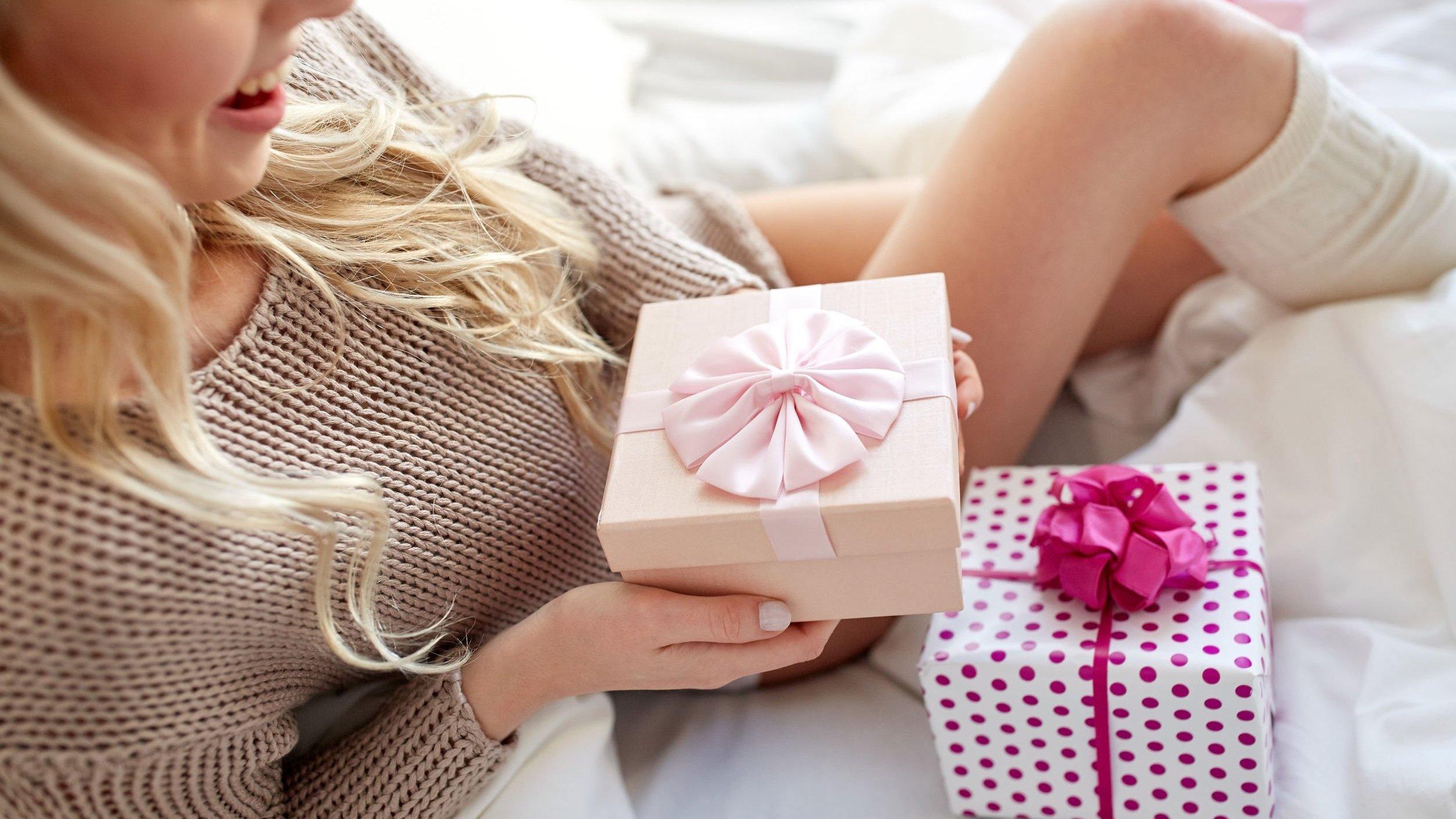 Mulher na cama com duas caixas de presente