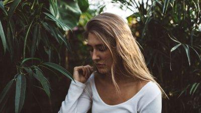 Mulher olhando para baixo no meio de plantas