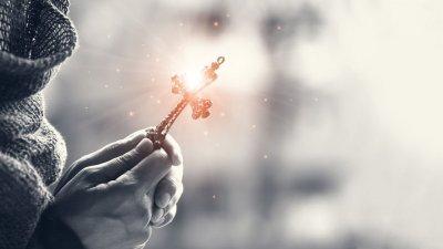 Mãos segurando crucifixo