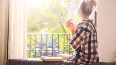 Mulher sentada na beirada do sofá segurando xícara de café e olhando para fora da janela